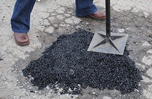 Kent Asphalt Paving employee stamping asphalt to repair a hole in Kent